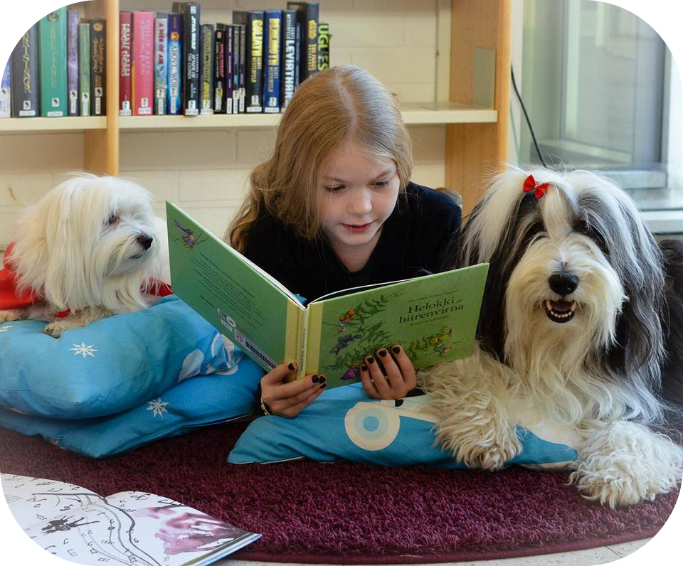 Little girl reading to two dogs