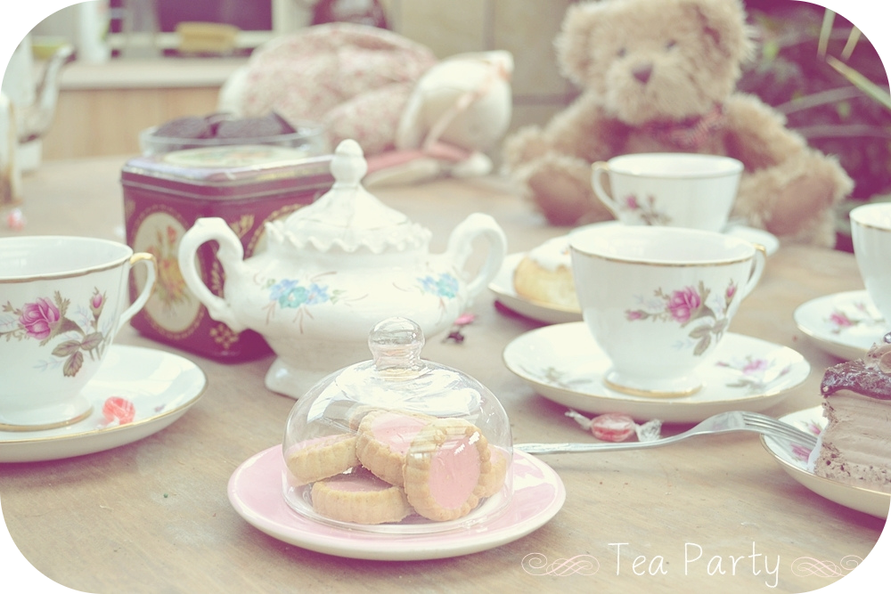 Child's tea party with a teddy bear in background.