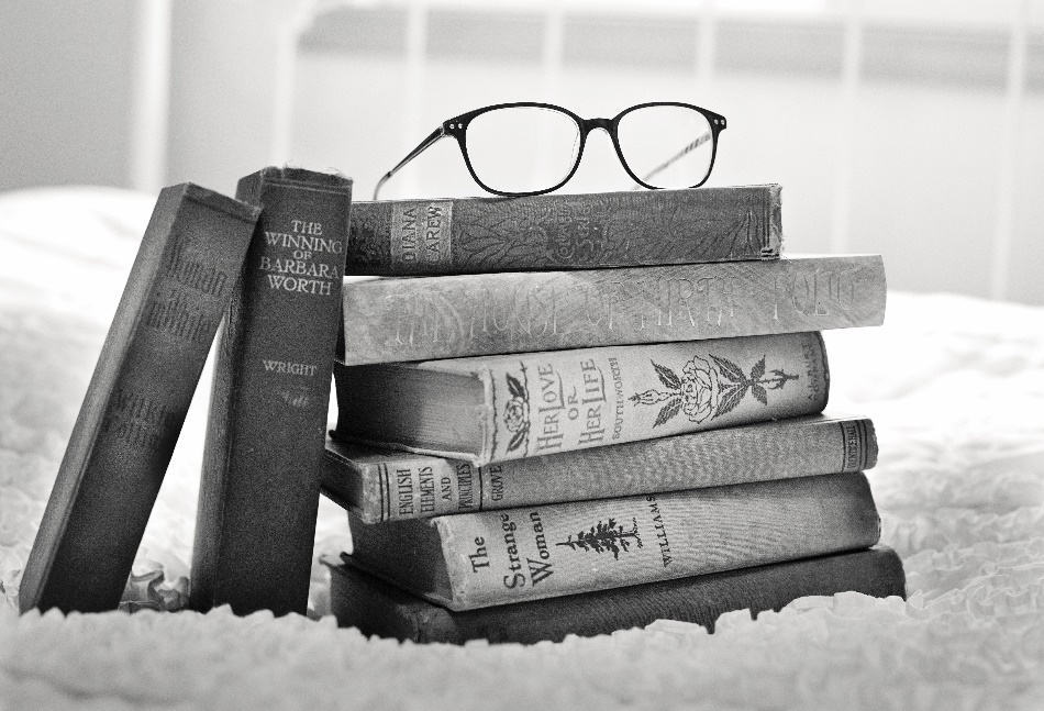 Stack of books with a pair of glasses resting on top of it