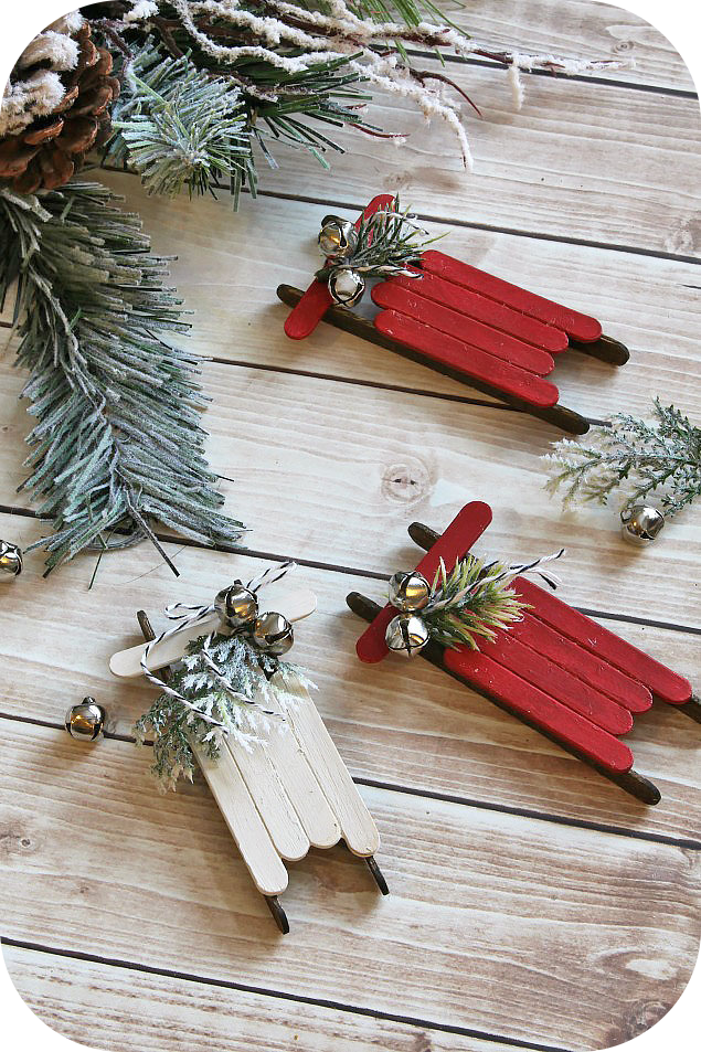 Holiday ornaments, miniature sleighs, evergreen boughs, bells