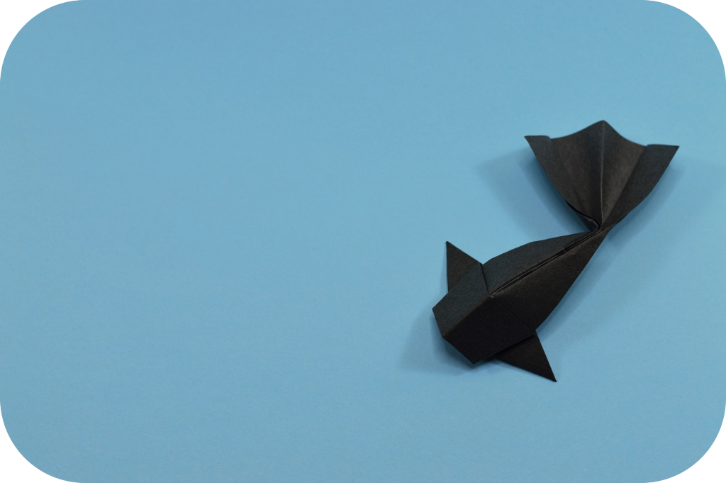 Black origami carp against blue background