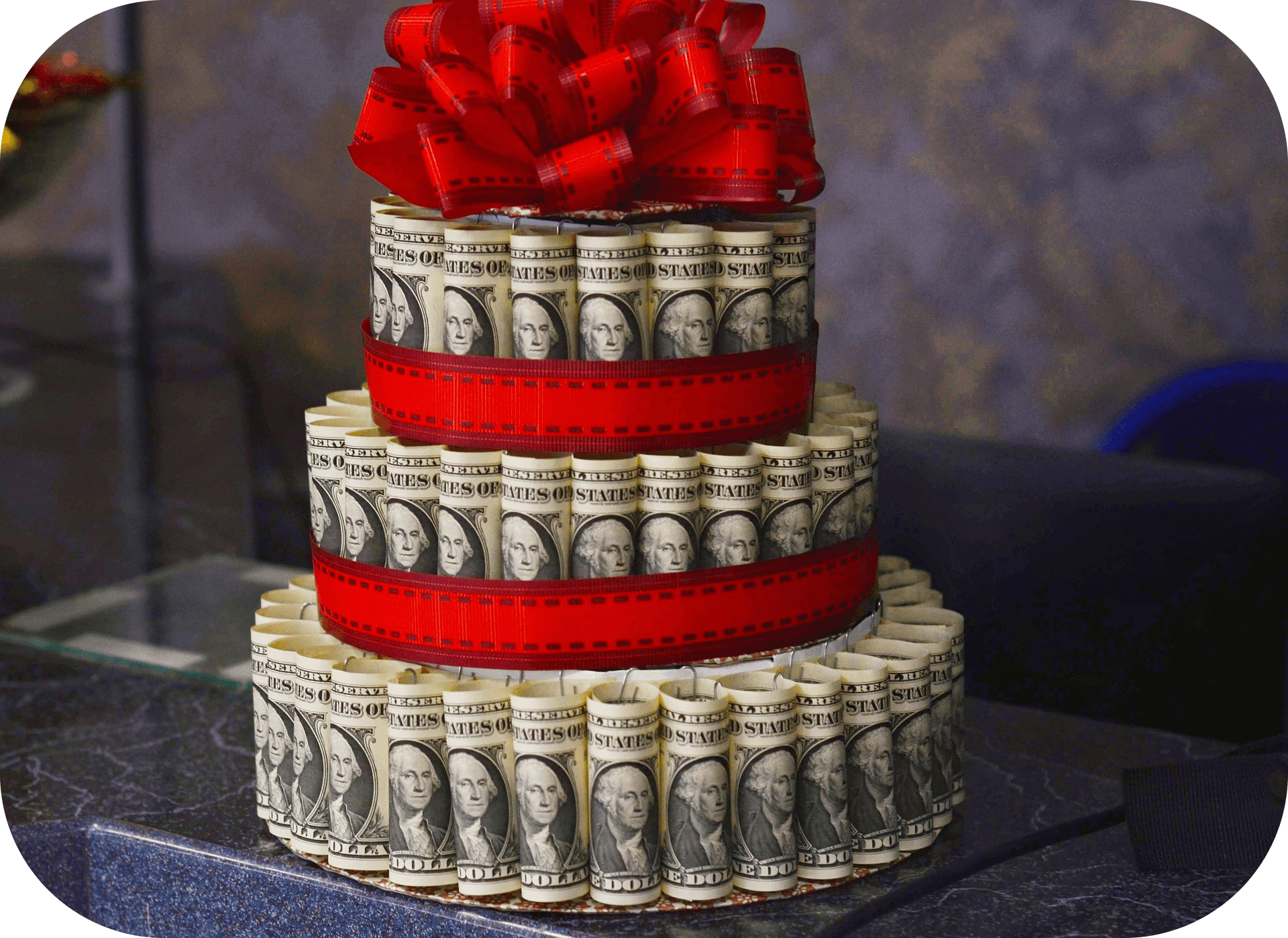 Dollar bills arranged to look like a layered cake, red ribbons