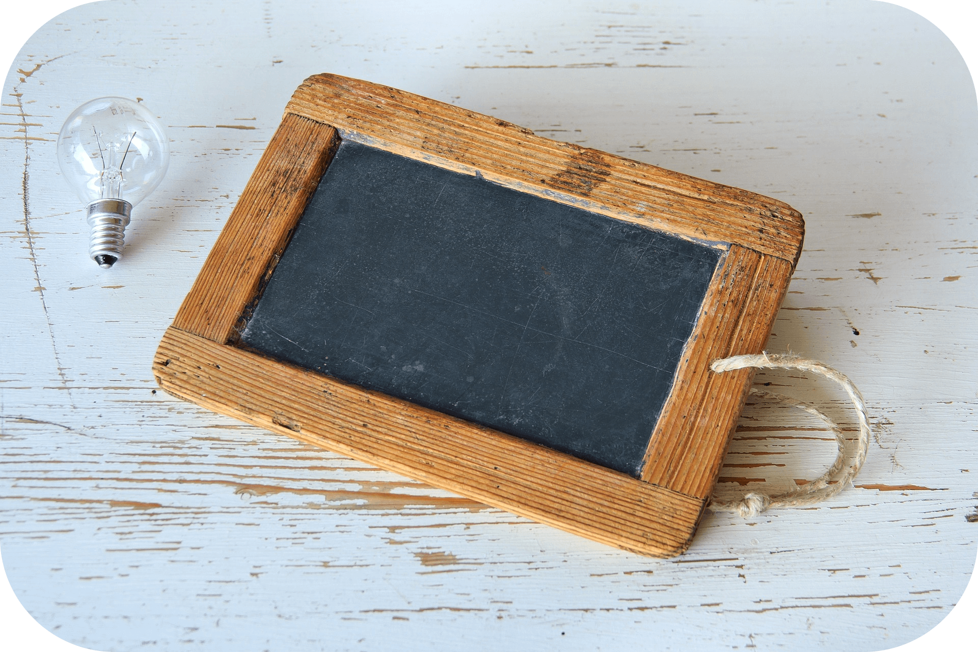 Weathered wooden table, light bulb, chalkboard