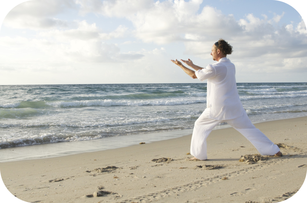 Beach, ocean, man practicing qi gong